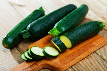 Closeup of fresh courgettes with chopped slices on wooden surface. Vegetarian food concept