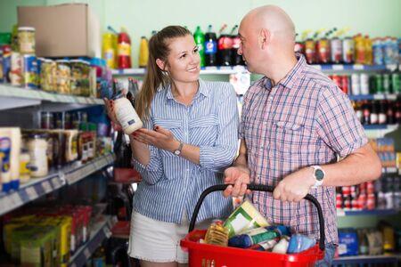 Positive woman and man choosing mayonnaise at food store Stock Photo