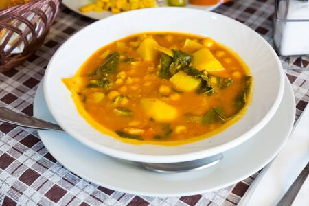 Dish of Spanish cuisine. Traditional thick chickpea soup with greens