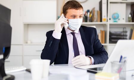 Portrait of man in disposable face mask working in business office talking on phone