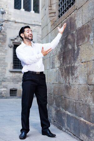 Handsome passionate man singing serenade love looking at lattice castle window
