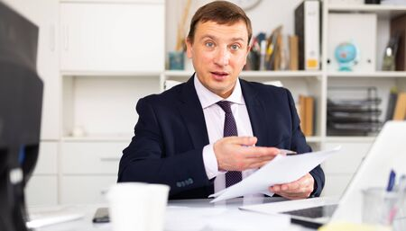 Middle-aged male worker engaged in business activities at workplace in office Фото со стока