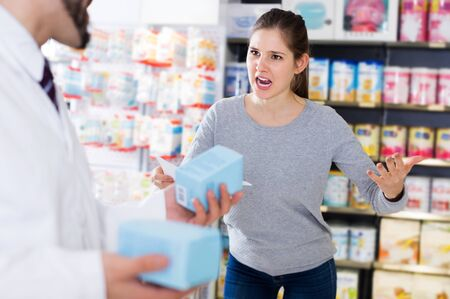 Portrait of outraged woman buyer with medicines in pharmacy