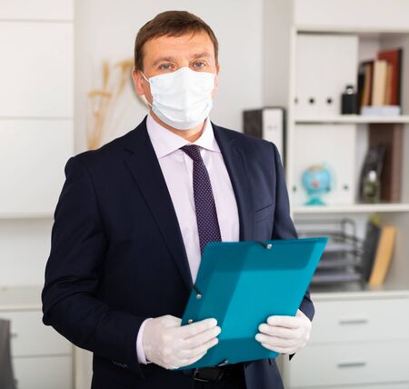 Man in disposable personal protective equipment welcoming to office, business process during pandemic situation Фото со стока