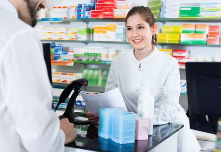 Diligent positive cheerful woman pharmacist is recommending medicine for man client in apothecary. Foto de archivo