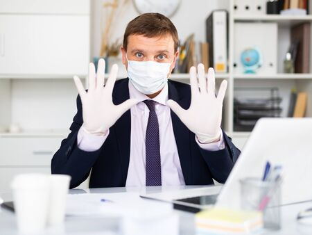 Male worker wearing medical facial mask and gloves engaged in business activities at table in office