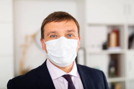 Portrait of businessman in disposable face mask standing in business office, new normal due to coronavirus outbreak Фото со стока