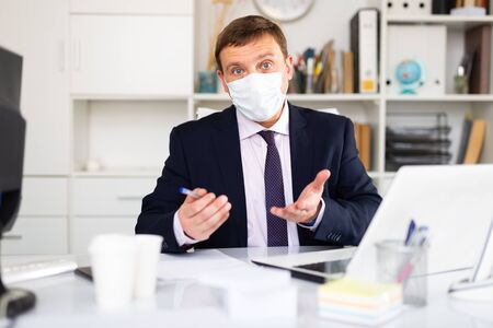 Focused male in disposable face mask working in business office using laptop, new normal due to coronavirus outbreak Фото со стока
