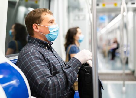 Focused man in medical face mask and protective gloves riding in modern subway car. Concept of forced city trip in context of coronavirus pandemic