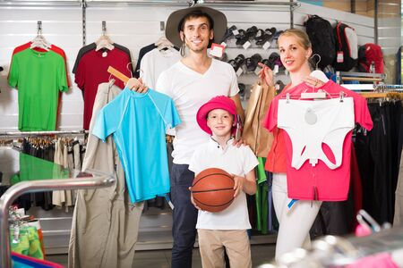 young russian  man and woman with boy choosing all for hiking in sport shop