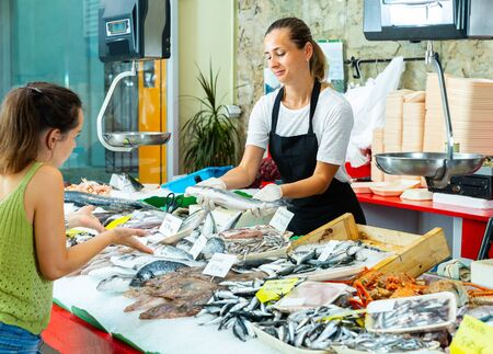 Confident female worker of fish store offering fresh sea bass to woman customer Stock Photo