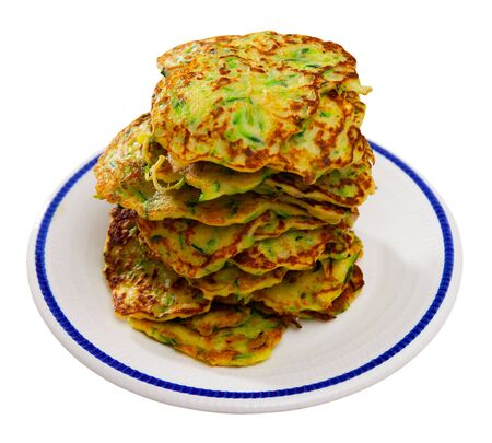 Stack of appetizing zucchini fritters on plate. Vegetarian snack. Isolated over white background