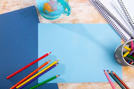 Multicolored pencils and notebooks on the table with place for text. School supplies