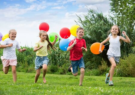 Playful kids running and laughting with multicolored balloons on green meadow