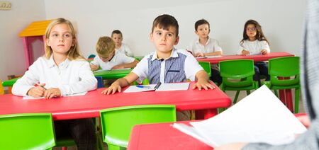 First person view of children at desks in classroom