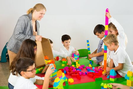 Cute schoolchildren creating constructions from toy blocks with teacher in classroom Фото со стока