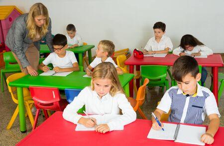 Female teacher helping schoolchildren doing their task in classroom