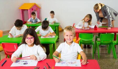 Cheerful school kids with pencils and drawing books studying in classroom with teacher