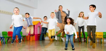 Positive cheerful smiling female teacher and group of schoolkids jumping in classroom Фото со стока