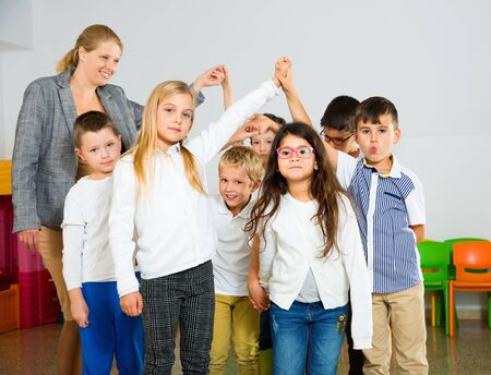 Positive smiling female teacher playing circle game with children in classrom