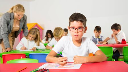 Little schoolboy drawing with color pencils at desk in classroom