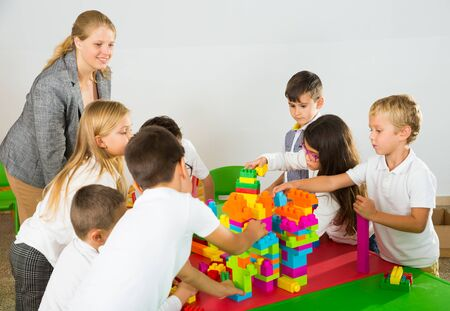 Young female teacher and happy schoolkids building castle from plastic toy blocks during lesson in classroom