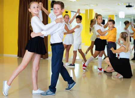 Diligent  smiling positive  boys and girls having dancing class in classroom Фото со стока