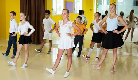 Happy boys and girls dancing in class with young woman instructor and smiling Stock Photo