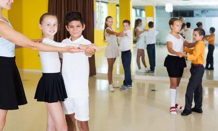 Smiling active children  dancing pair dance in class