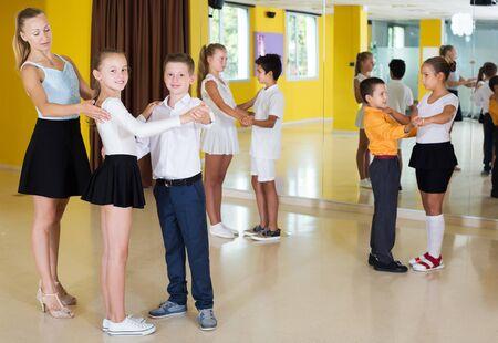 Positive young children  enjoying of partner dance in class Фото со стока