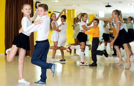 Young boys and attractive girls enjoying active dance in studio