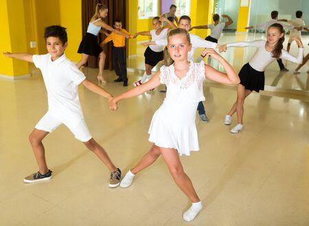 Happy boys and girls enjoying active dance in studio