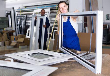 Young european female worker measuring metal-plastic window frame in workshop