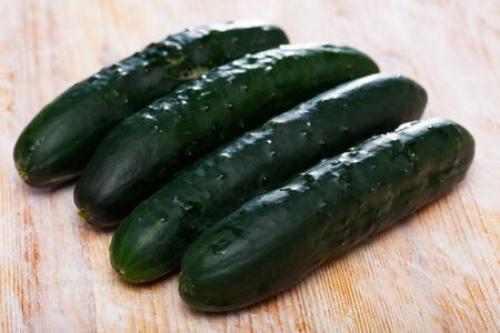 Closeup of organic cucumbers on wooden background. Healthy nutrition concept Imagens