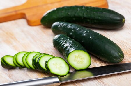 Whole and sliced fresh cucumbers on wooden table. Healthy vegetarian ingredient