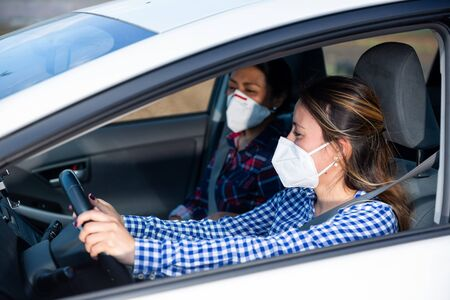 Young Hispanic woman in medical face mask driving car with female friend in front passenger seat. Concept of new life reality and health protection in coronavirus pandemic Stok Fotoğraf