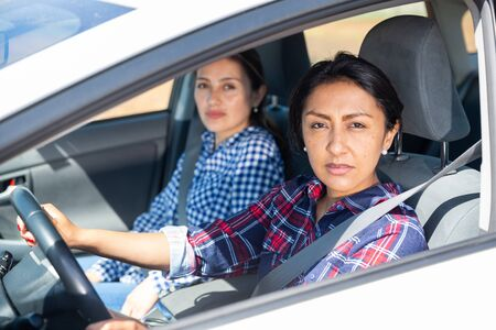 Portrait of focused Latin American woman driving car with girl sitting in passenger seat