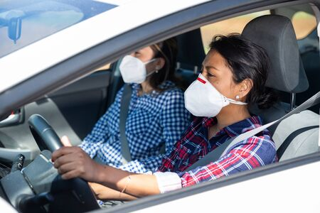 Hispanic women wearing personal protective equipment while driving a car Stok Fotoğraf