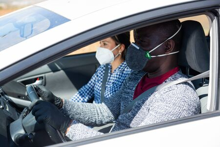 African american man in protective face mask and gloves driving car with girl in passenger seat. Concept of infection prevention and control of coronavirus pandemic