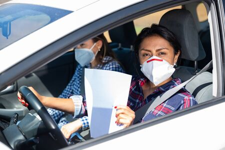 Portrait of middle aged Hispanic woman in medical face mask driving car, holding blank white sheet of paper, copyspace. Concept of control of coronavirus pandemic