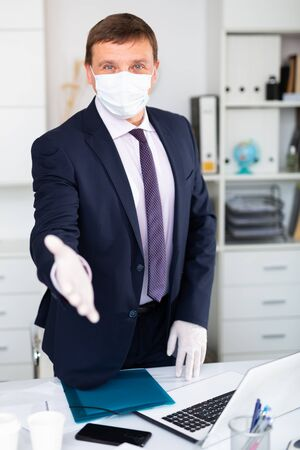 Positive businessman in medical face mask stretching open hand in rubber gloves offering handshake and inviting to office. Concept of precautions and social distancing in coronavirus pandemic