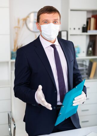 Man in disposable personal protective equipment welcoming to office, business process during pandemic situation