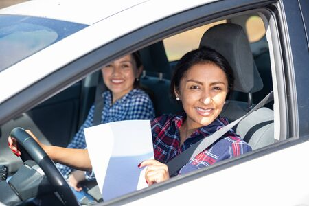 Portrait of smiling Peruvian woman driving car, holding blank white paper with copyspace