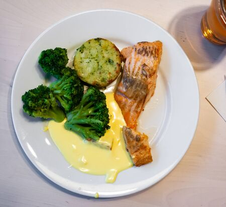 Baked salmon fillet with vegetables and sauce served on plate Stok Fotoğraf