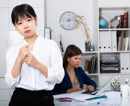 Unhappy and crying asian woman standing in office with working colleague behind