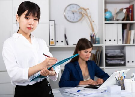 Asian girl manager of international company greeting guests in office
