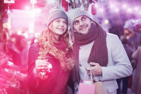 Smiling girl with boy choosing decorations at Christmas market Stock fotó