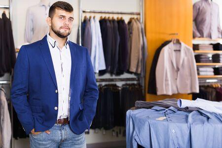 Brunette male customer choosing jacket in men clothes shop