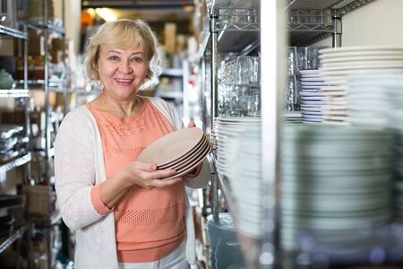 female buyer with clay plates in the tableware store near the shelf