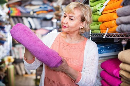 Glad cheerful  mature woman holding cotton colour towel in the textile shop